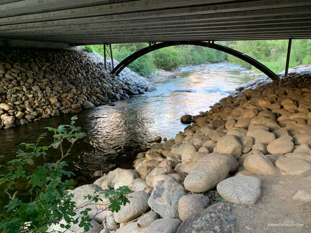 A bridge over a river with rocks lining each bank