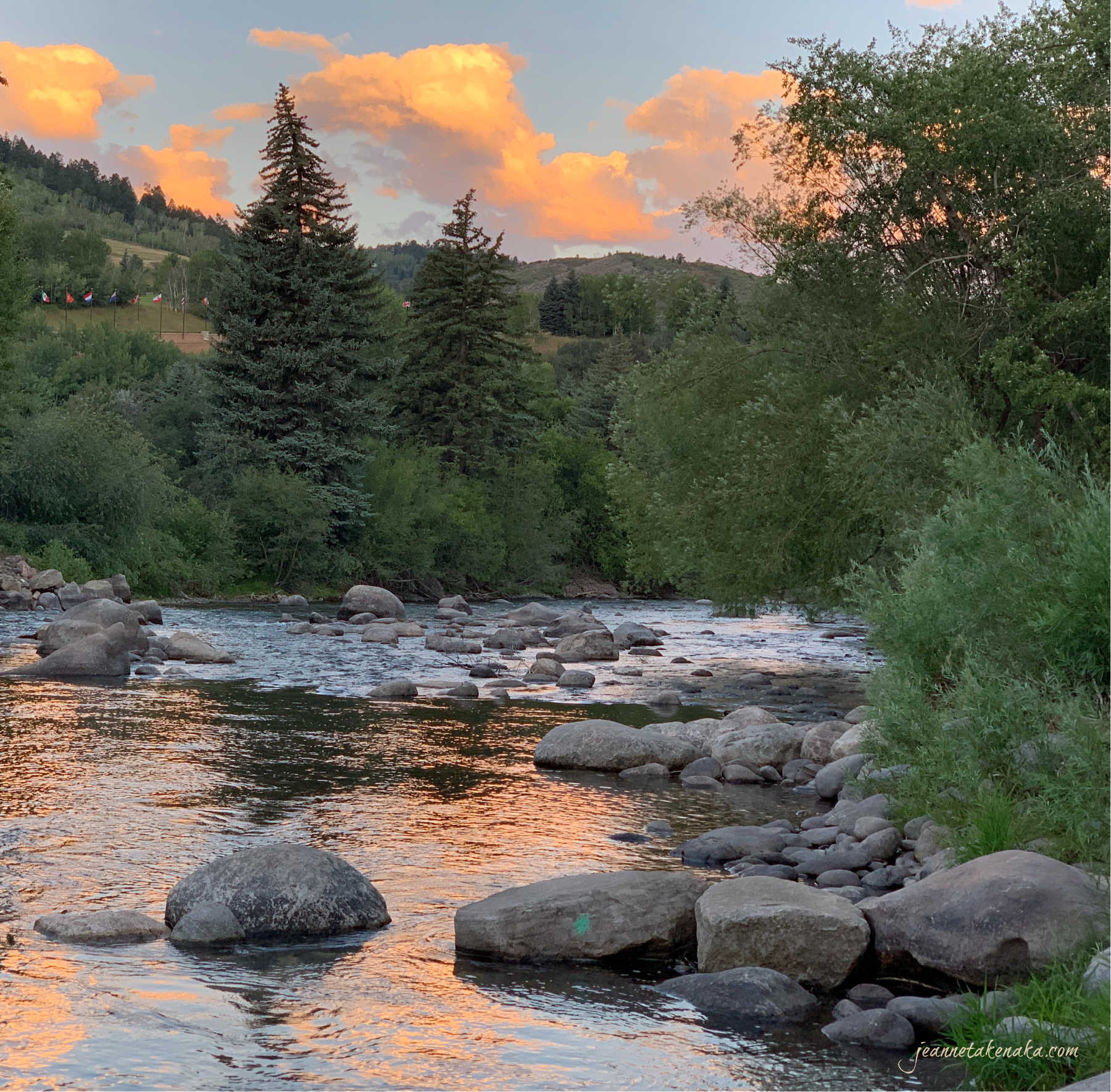 A river with sunrise-colored clouds reflecting on its surface, interrupted by rocks