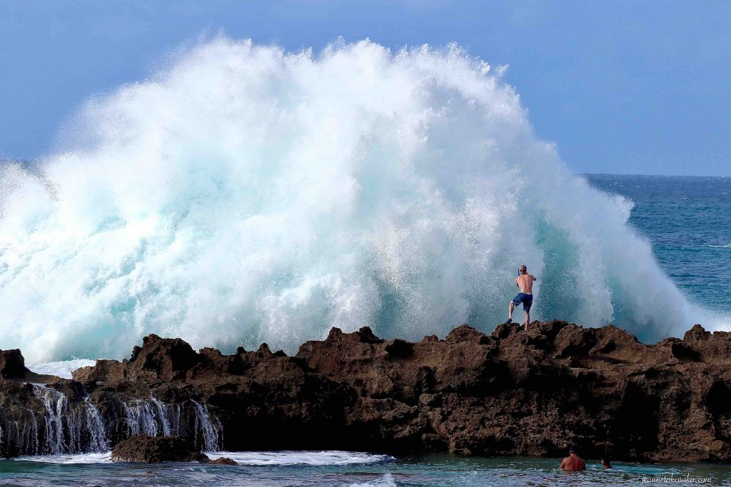 A man snapping a close-up photo of a huge crashing wave