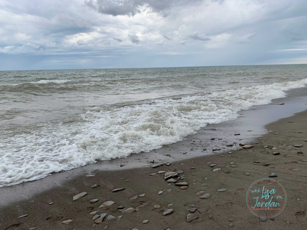The ocean rolling onto a rocky, sandy shoreline