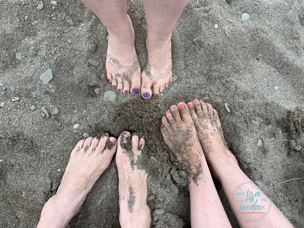 A photo of three sets of feet in sand-friends spending time together, nurturing friendships.