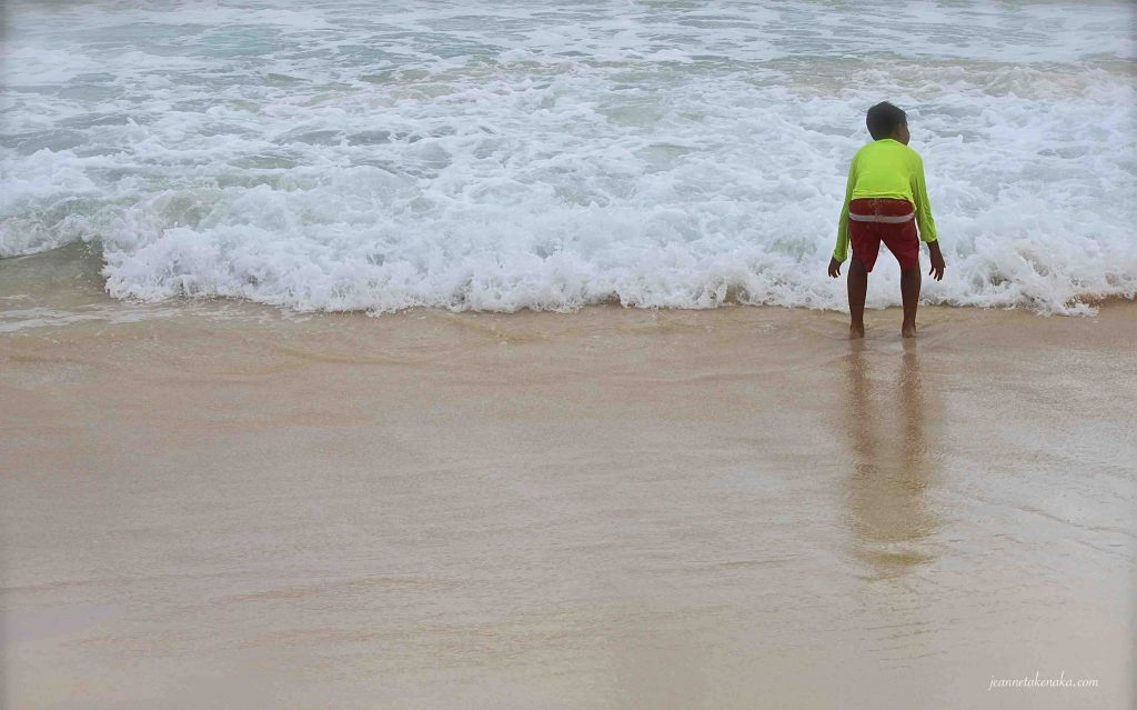 A boy standing at the edge of a wave rolling into shore