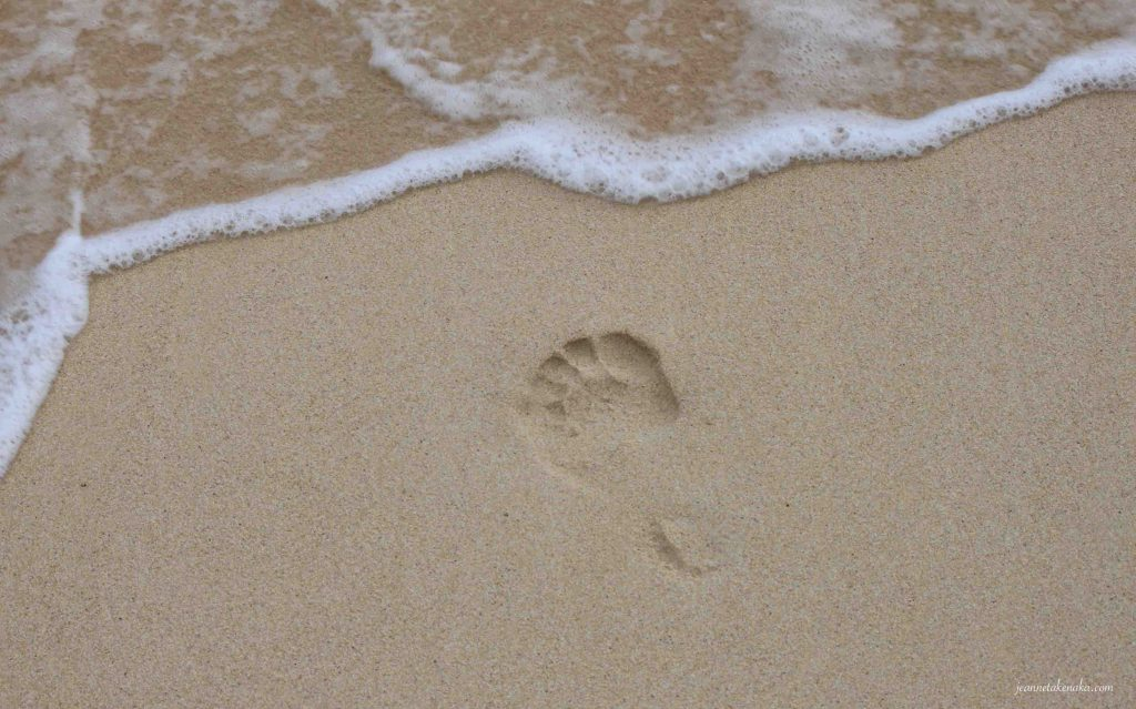 One footprint at the edge of an oncoming wave on a beach. When we deal with fear and our heart stops clinging to it, we can face things