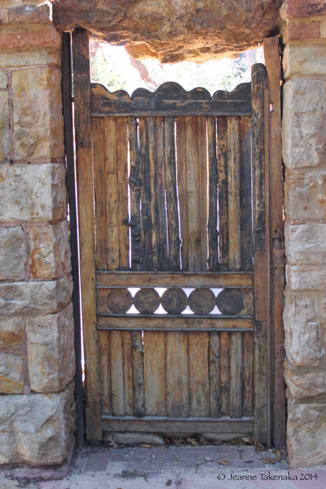 A closed rough-hewn wooden door set in a rock wall