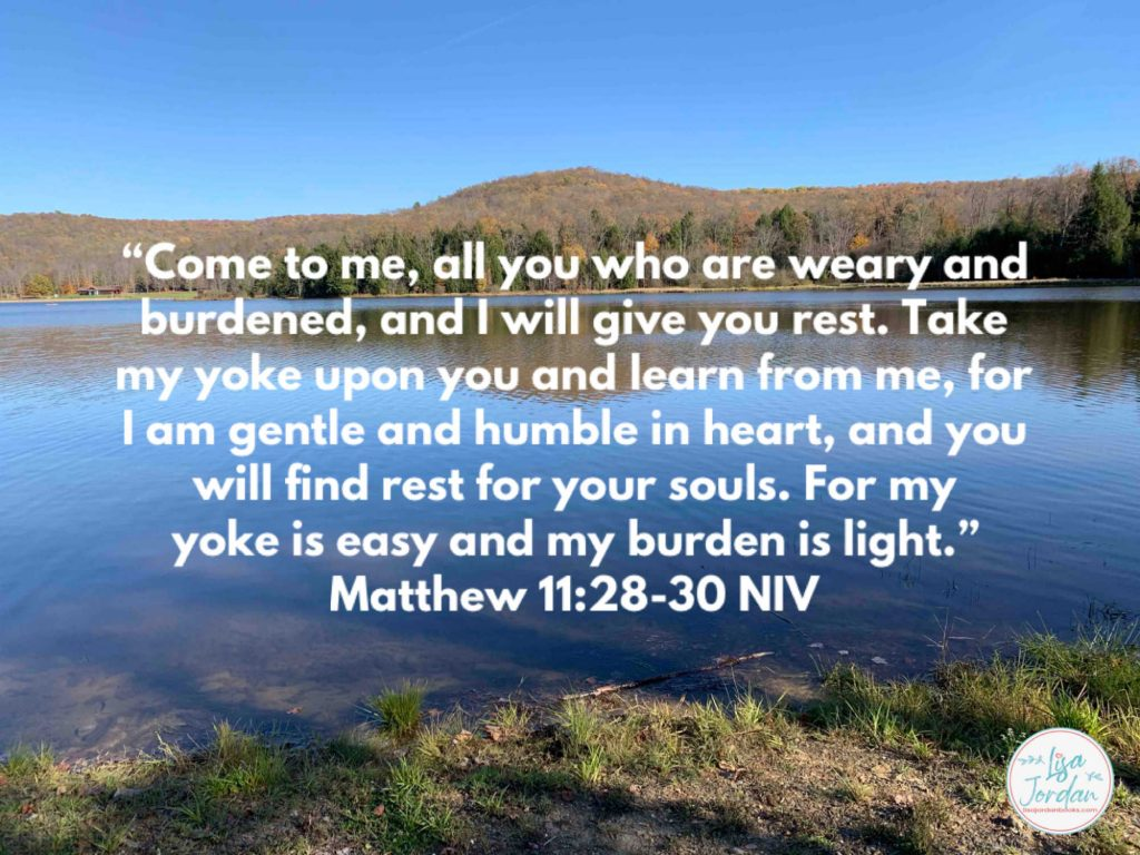 """Meme: """"'Come to me, all you who are weary and burdened, and I will give you rest. Take my yoke upon you and learn from me, for I am gentle and humble in heart, and you will find rest for your souls. For my yoke is easy and my burden is light.'"""" ~Matthew 11:28-30 NIV on a backdrop of a lake and trees on the far bank"""