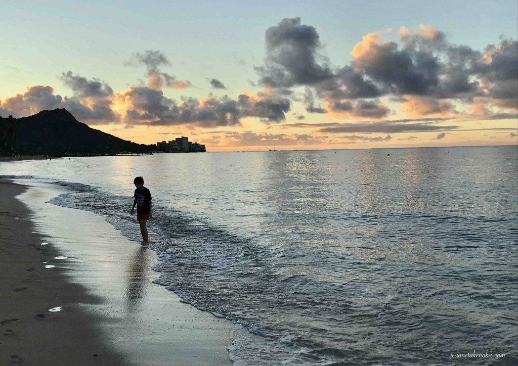 The silhouette of a boy alone on the beach at sunrise