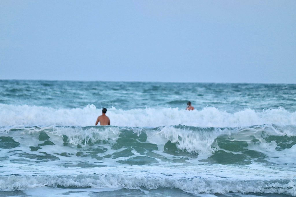 A surfer stands between two frothy waves