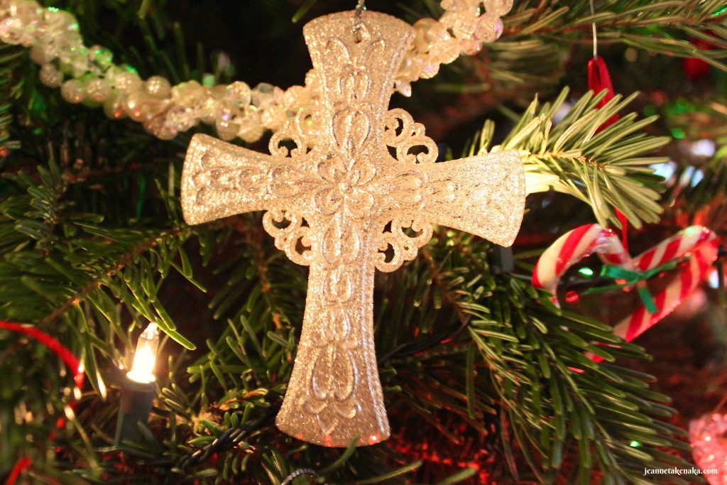 A creamy cross ornament hanging on a Christmas tree, a reminder of the gift of redemption that Jesus gave as Emmanuel