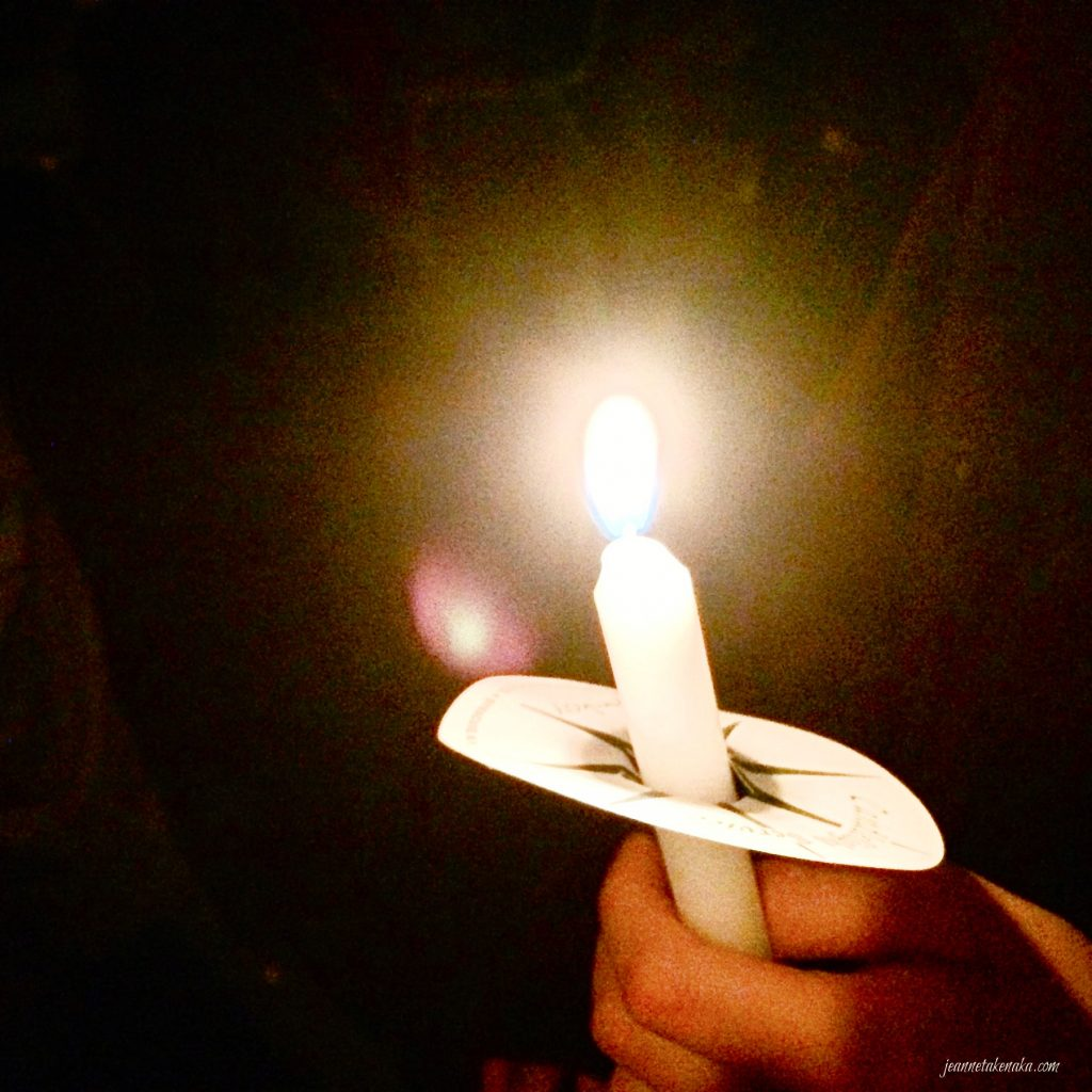 A hand holding a candle with bright light, symbolic of Jesus being the light of the world and being with us.