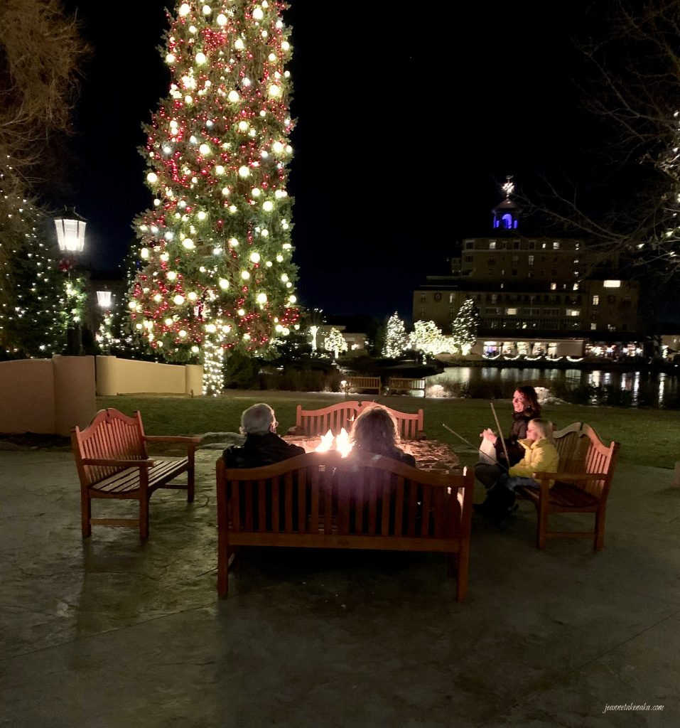 People sitting around a fire pit with Christmas lights offering the lighting