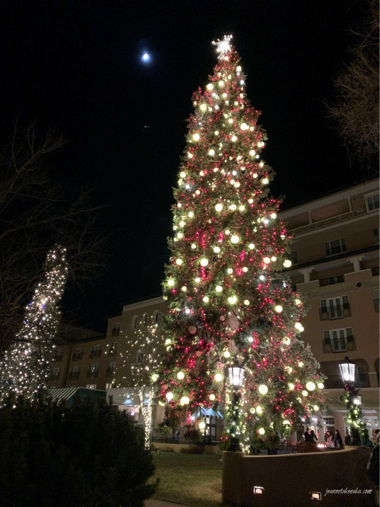 A tall Christmas tree glowing with the backdrop of the night sky and the moon