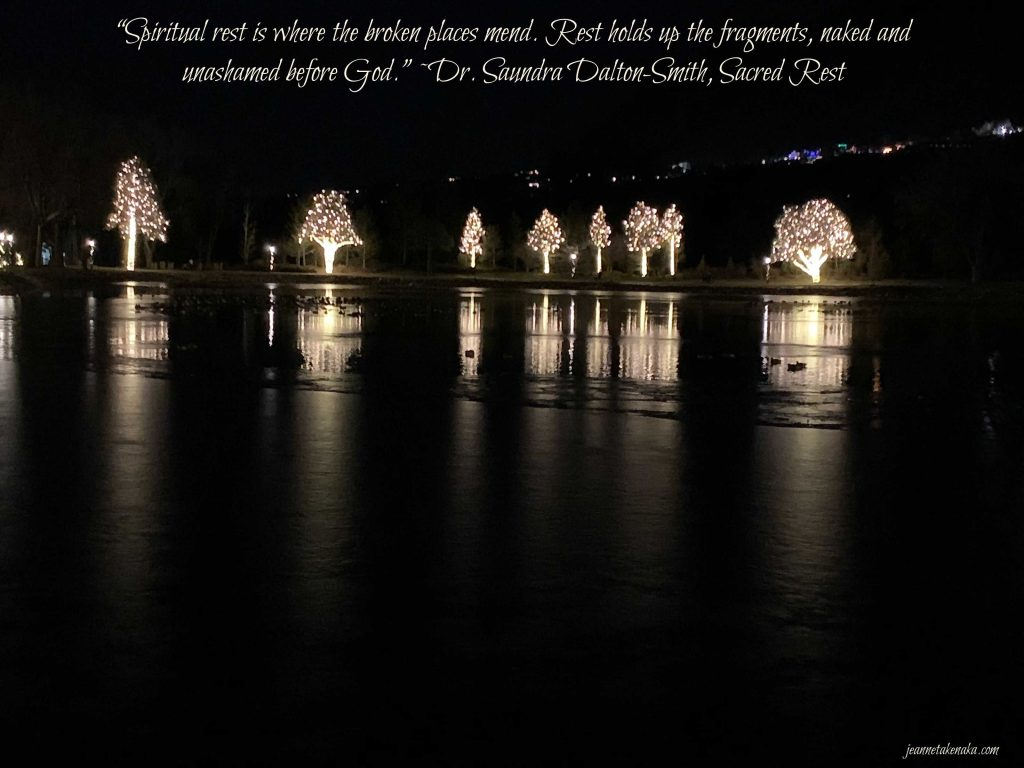 """A meme that says, """"Spiritual rest is where the broken places mend. Rest holds ups the fragments, naked and unashamed before God."""" ~Dr. Saundra Dalton-Smith on a backdrop of lit up trees reflecting into a frozen pond"""