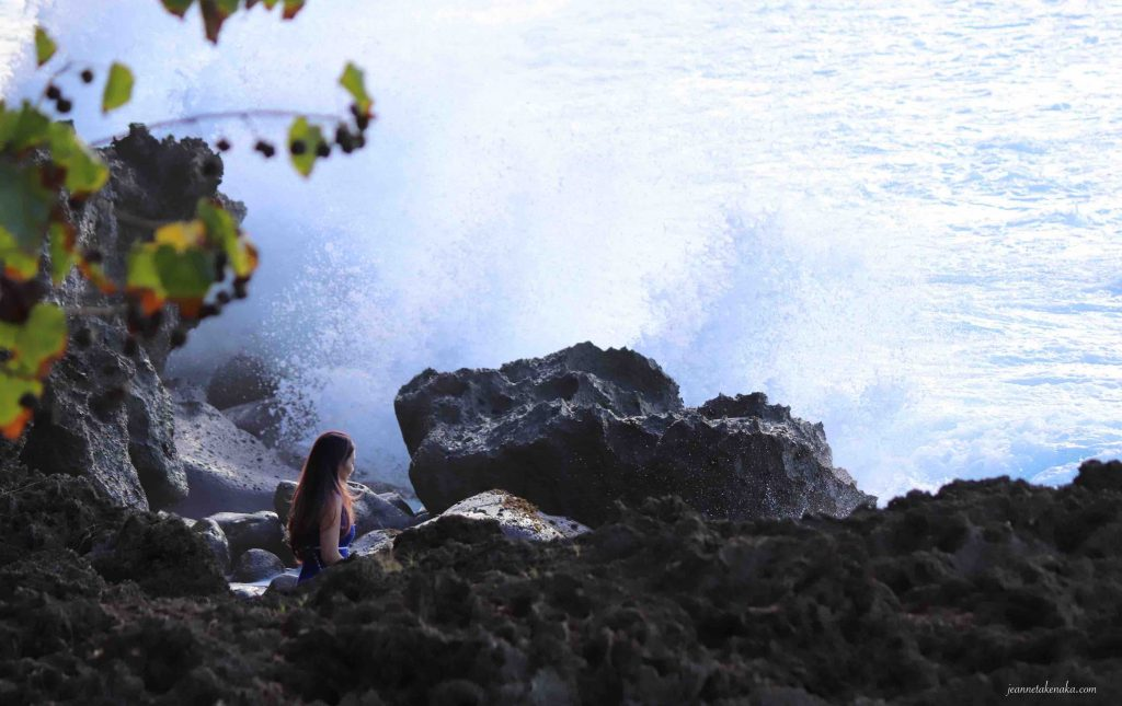 A woman standing in a cleft of rocks with large waves crashing nearby
