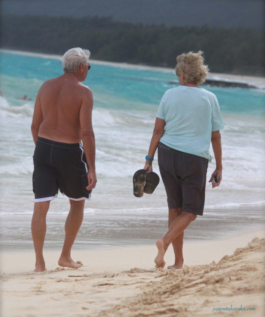 A couple walks along the beach