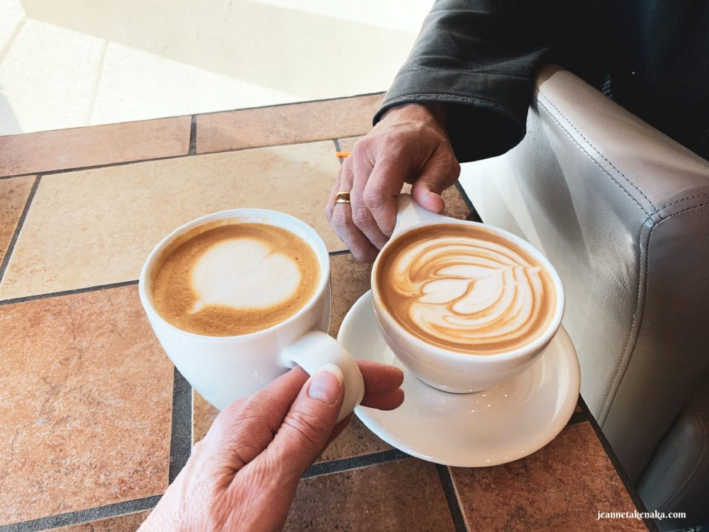 Two coffee drinks on a table with hands reaching for each . . . husband and wife talking
