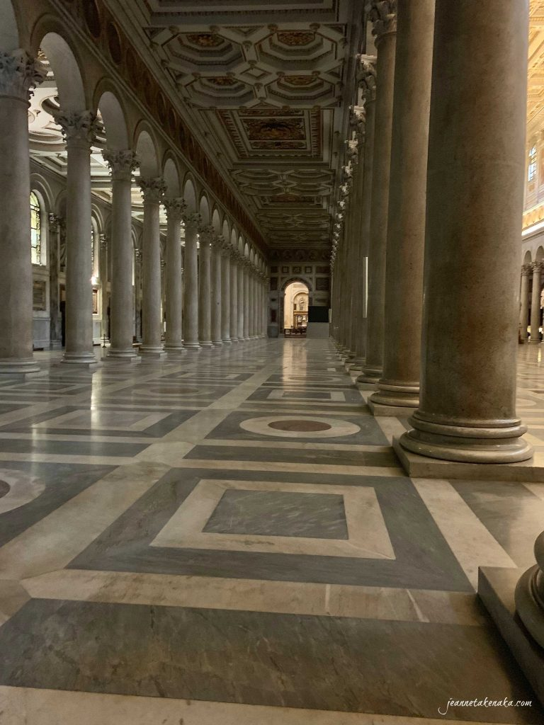 An image of a long, marble-columned passageway in a cathedral.