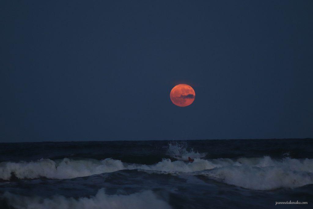 A red moon rising above an ocean and beach