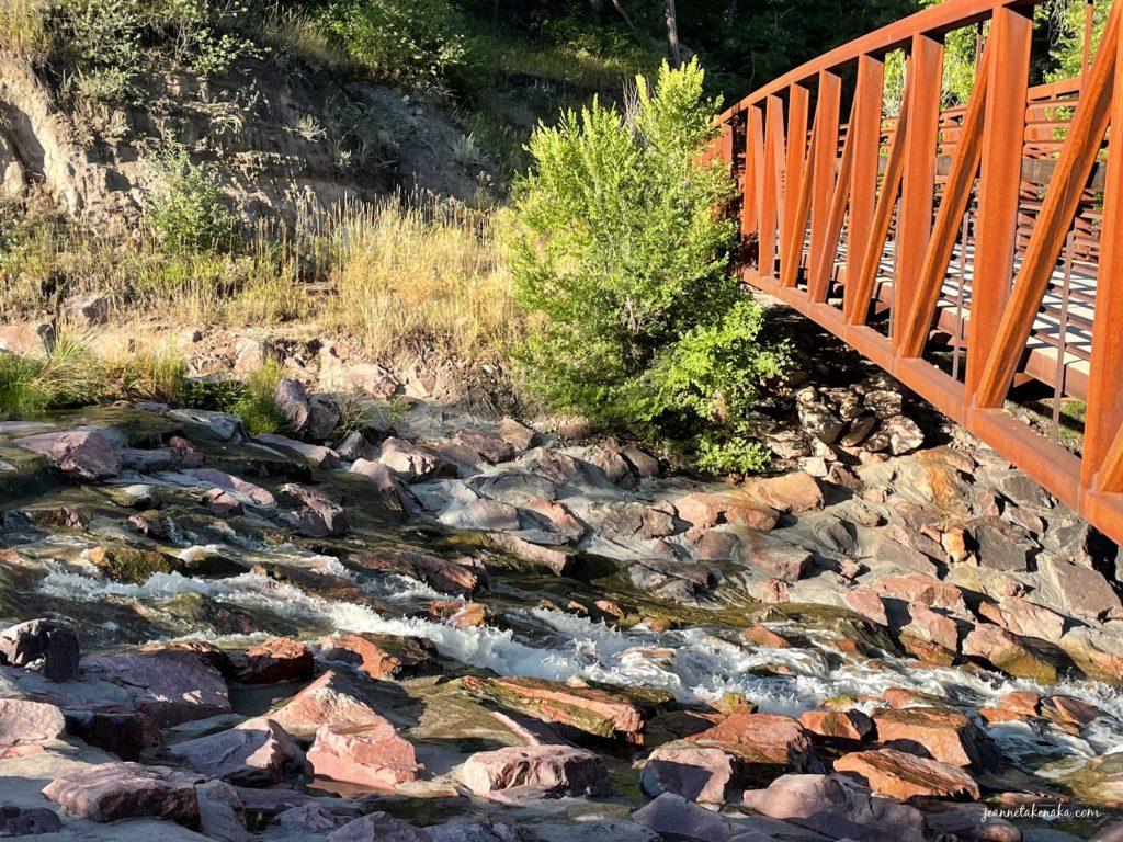 Water flowing downhill under a metal bridge